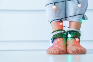 Female legs in warm knitted soft cozy christmas socks and garland with illuminated lights in wintertime at home. Copy space
