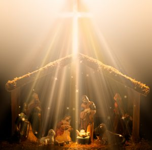 Christian nativity scene glowing in heavenly rays of light with the baby Jesus glowing in the center.