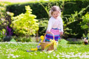 Little girl playing in sunny garden. Baby on Easter egg hunt in flower meadow. Toddler child with decorated basket picking colorful eggs, chocolate and sweets. Kids play outdoors. Fun for children.