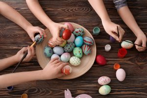 Cute little children painting eggs for Easter at table