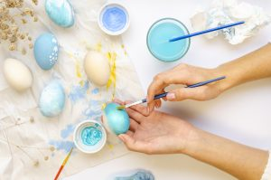 Easter eggs painting process. Feminine hands with paint brushes on a white background. Cozy warm colors. Top view.