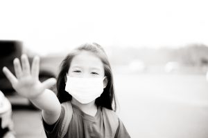 Covid-19 and Air pollution pm2.5 concept.Little chinese girl wearing mask for protect pm2.5 and show stop hands gesture for stop corona virus outbreak.Wuhan coronavirus and epidemic virus symptoms.